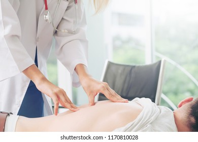 Woman doctor is examining male patient in hospital office. Healthcare and medical service.
