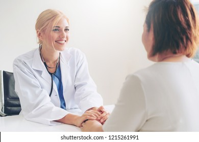 Woman doctor holds patient hand patient in room of hospital office. Healthcare and medical service.