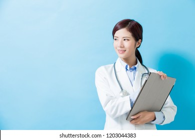 woman doctor look somewhere and take tablet pc on the blue background
