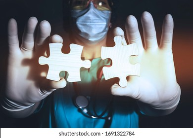A woman doctor in a medical mask, glasses and gloves holds two pieces of wooden puzzles. Closeup of the puzzle pieces