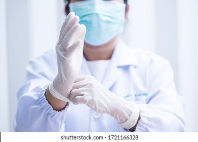 Woman doctor putting white latex medical gloves on white wall background.Surgeon wearing gloves before surgery at operating room.Risk management protection health care concept.