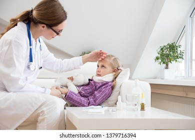 woman doctor sits at the bedside of the sicklittle girl  and measures the temperature