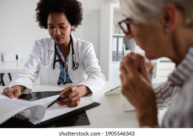Woman doctor sits at her office and examining elderly female patient