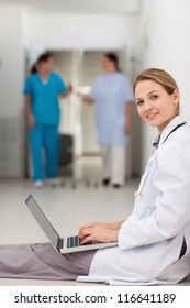Woman doctor sitting on the floor while typing on a laptop in a hallway