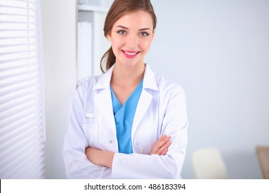Woman doctor is standing near window with crossed arms
