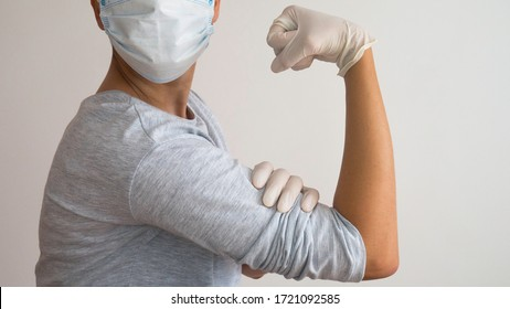 "Woman doctor with a surgical mask and white rubber gloves in position of  Rosie the Riveter ""We Can Do It!"""