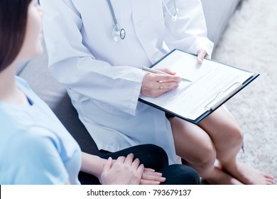 Woman doctor talking to her male patient at office