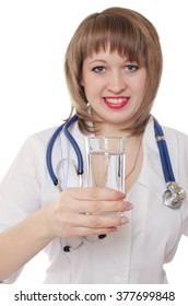 The woman the doctor in a white dressing gown with a stethoscope on a neck holds a glass with water in hand and smiles