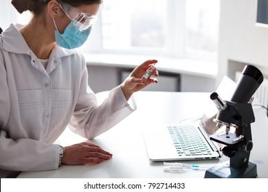 Woman doctor working in the lab at the laptop