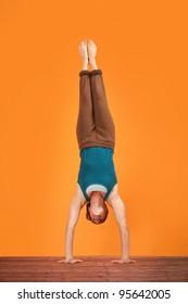 Woman does Adho Mukha Vriksasana yogasana upside down