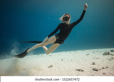 Woman does freediving in the sea among corals, soft sunlight rays penetrate the water