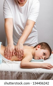 Woman does massage to the little boy