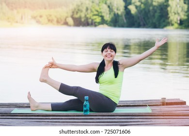 Woman does yoga on the bridge in the summer. Toning.