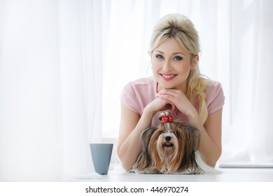 Woman with dog. Beautiful young woman training her small Maltese dog at home. Portrait of smiling girl