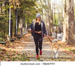 Woman and dog jogging in the park.