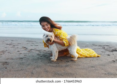 Woman And Dog On Beach. Beautiful Girl Hugging Pet On Dog-Friendly Coast. Asian Model Enjoying Walk With Cute Puppy On Summer Vacation At Tropical Ocean. Fashion Female In Trendy Bohemian Dress.