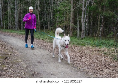 Woman with a dog on a run in the park