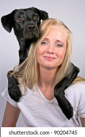 Woman with dog over her shoulder smiling