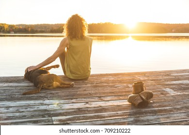 Woman and dog relaxing on the dock at sunset. Autumn colors, unstaged situation with candid model and her dog. Relaxation and friendship concepts.