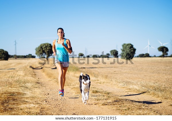 Woman and dog running in country side dirt track. Female runner exercising and training with her pet for cross race. Fitness girl on summer rural landscape.