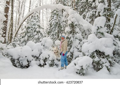 A woman with a dog in a snow-covered winter forest