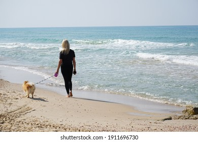 Woman with a dog for a walk along the sea