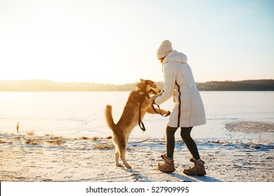 woman with dog walking down the village street in the snow
