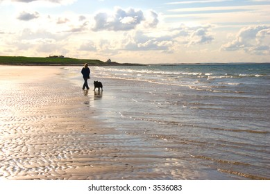 Woman and dog walking on deserted beach under evening sky