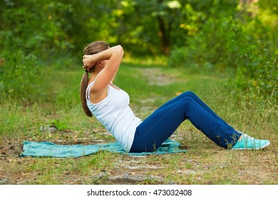 Woman doing abdominal exercise  in park.