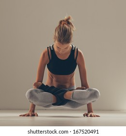 Woman doing an arm balancing yoga exercise.