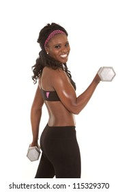 a woman doing an arm curl with a weight with a smile on her face.