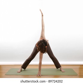 Woman doing an arm extension yoga pose om a green mat