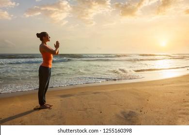 Woman doing Ashtanga Vinyasa Yoga asana Tadasana Samasthiti yoga posture on beach on sunset