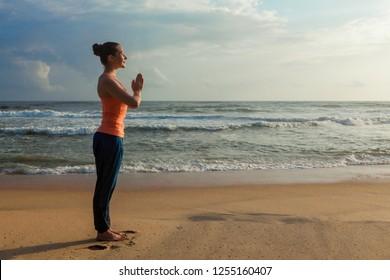 Woman doing Ashtanga Vinyasa Yoga asana Tadasana Samasthiti yoga posture on beach