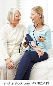 Woman doing blood pressure monitoring for senior woman at home