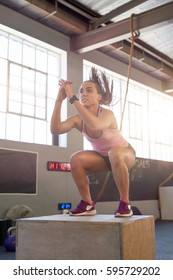 Woman doing box jumps in gym, intense workout determination and strength lots of natural light