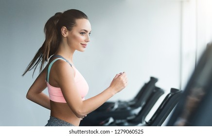 Woman doing cardio training on treadmill, working out in gym