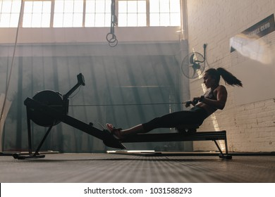 Woman doing cardio workout on rowing machine in the gym. Female exercising in fitness club.