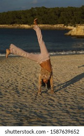 Woman doing cartwheel at the beach
