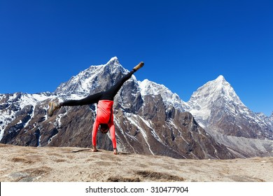 Woman doing cartwheel high up in the Himalayas mountain