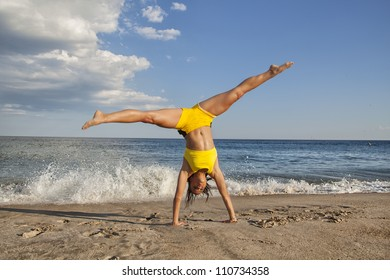 woman doing cartwheel on the beach fit female