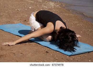 a woman doing childs pose on her mat on the beach.
