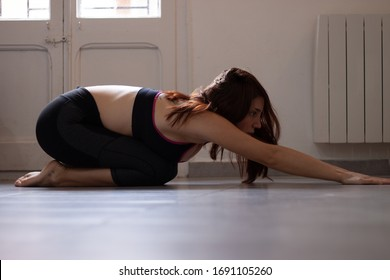 Woman doing childs pose in yoga class in home