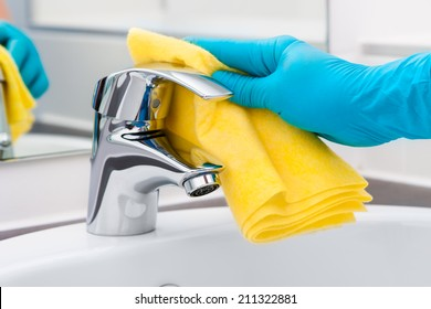 Woman doing chores in bathroom, cleaning of water tap
