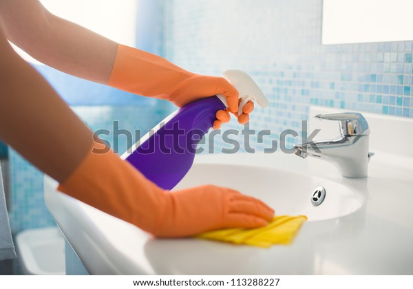 woman doing chores in bathroom at home, cleaning sink and faucet with spray detergent. Cropped view