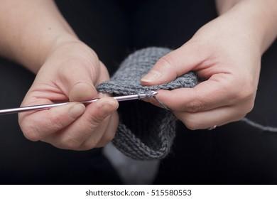 Woman is doing crochet. A closeup shot of a caucasian woman doing handmade socks.