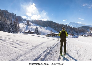 Woman doing cross-country skiing on groomed trail in snow-covered winter landscape with sunny weather and beautiful mountains in background