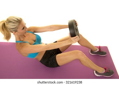 a woman doing a crunch with a weight.