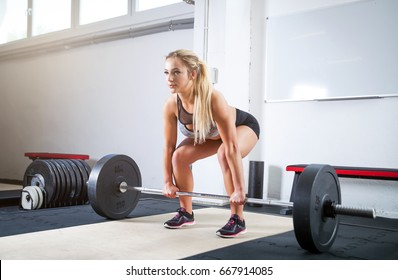 Woman doing deadlift exercise, weight lifting workout at the gym
