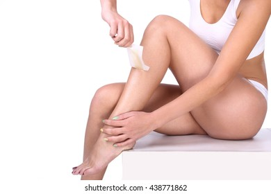 woman doing depilation on her legs with waxing, isolated on white